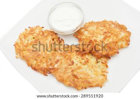 potato pancakes with sour cream on a white plate - stock photo