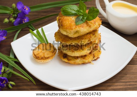 Potato pancakes with sour cream sauce on the background color. Wooden table. Close-up