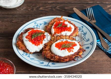 Potato pancakes with yogurt and red caviar - stock photo