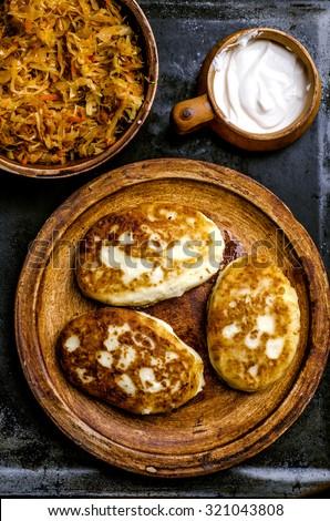 Potato patties with stew cabbage.Ukrainian cuisine. Dark moody style.Top view - stock photo