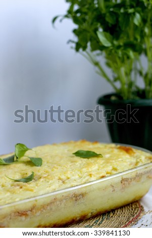 Potato pudding with basil leaves. Focus at potatoes pudding - stock photo