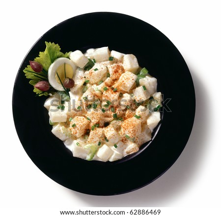 Potato salad in a black bowl, isolated on a white background.