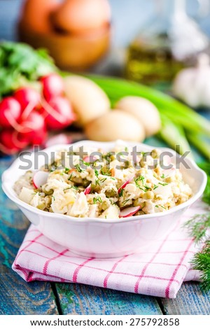 potato salad with fresh radishes and dill in a white bowl on a rustic wooden table - stock photo