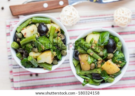 Potato salad with green beans, olives, capers, onions, delicious healthy diet rustic lenten dinner - stock photo