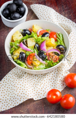 Potato salad with olives, tomatoes, lettuce, red onion, Italian dish, delicious food