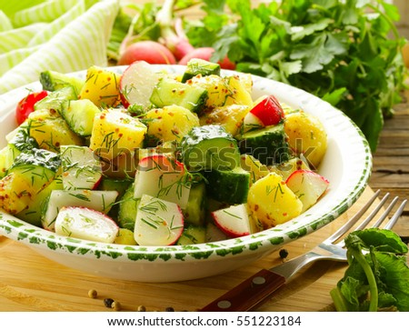 Potato salad with radishes and cucumbers, mustard dressing.