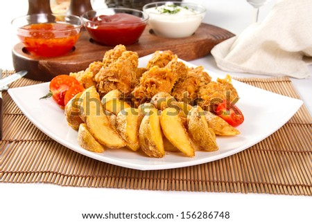 Potato wedges and fried chicken - stock photo