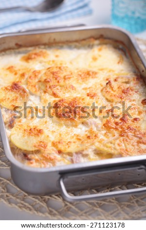 Potatoes a la dauphinoise in a baking dish. Selective focus on the potato crust - stock photo