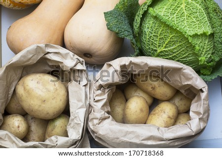 Potatoes, cabbage and butternut squash in drawer. - stock photo