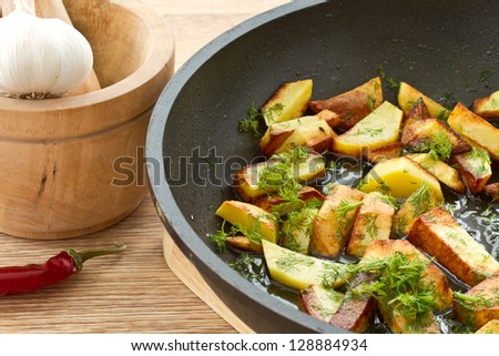 potatoes fried in oil in a frying pan with dill - stock photo