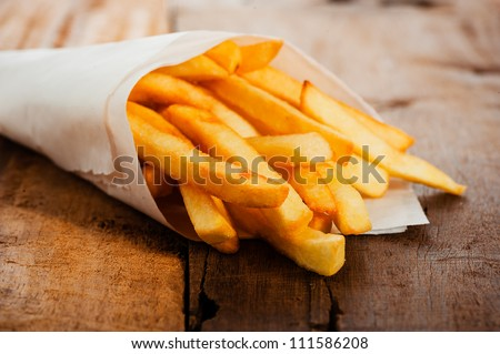 Potatoes fries in a little white paper bag on wood board - stock photo