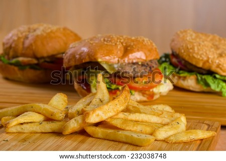 Potatoes fries in a little white paper bag on wood board with burgers on background - stock photo