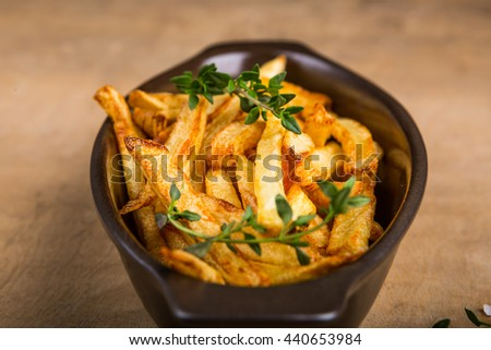 Potatoes fries in the bowl with salt and thyme - stock photo