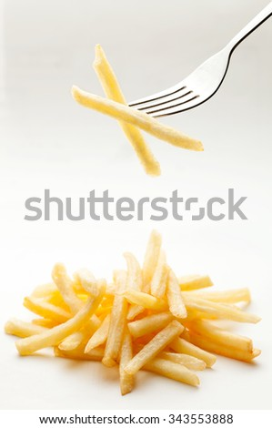 Potatoes fries on a fork - stock photo