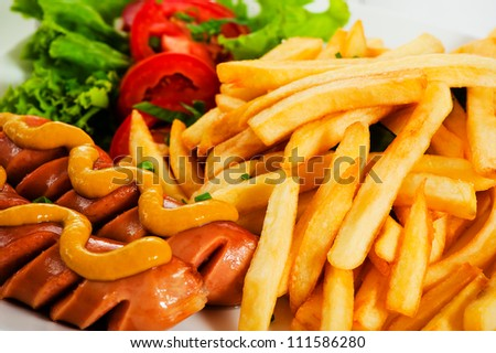 Potatoes fries with sausage mustard and tomato salad - stock photo