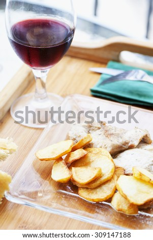 Potatoes, meat and wine over wooden tray, vertical image - stock photo