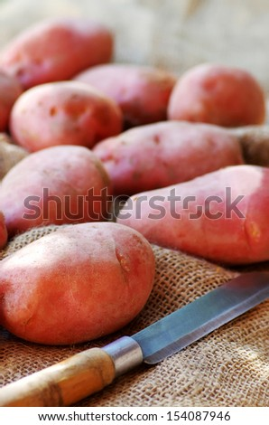 Potatoes of red peel and knife on table
