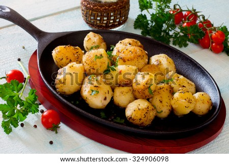 Potatoes on a cast iron pan, light derevyannytsy table