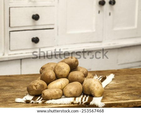 Potatoes on a textile on wooden table in the kitchen. - stock photo