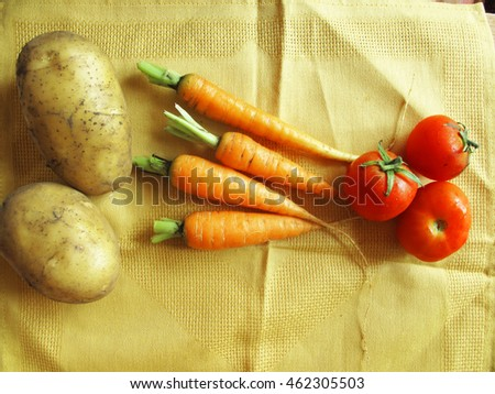 Potatoes, orange carrots and red fresh tomatoes on yellow tablecloth