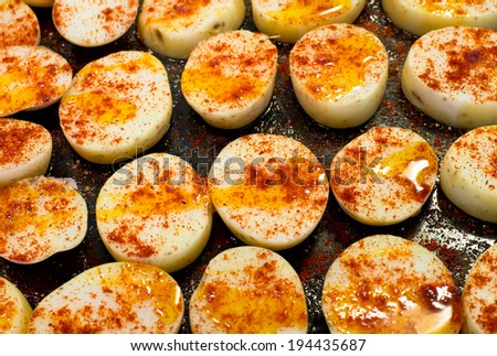 Potatoes slices covered by red pepper and olive oil before cooking.