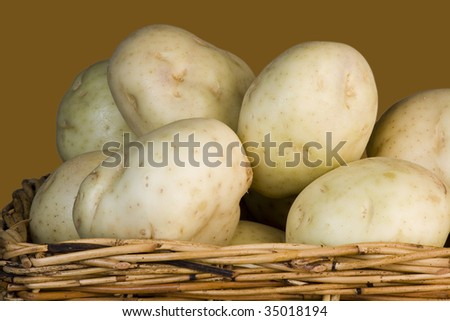 Potatoes stacked in a cane woven basket - stock photo