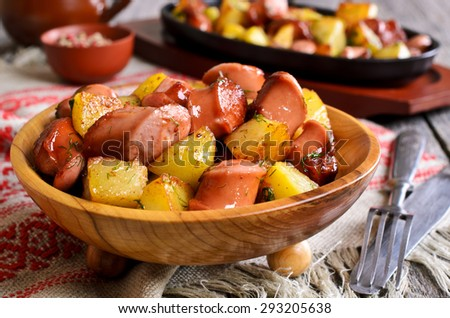 Potatoes with sausages, cut into slices and fried in oil, in rustic style - stock photo