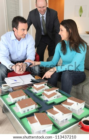Potential buyers looking at a housing model - stock photo