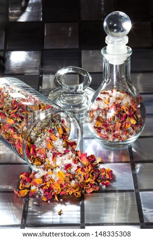 Potpourri with a mixture of colourful dried rose petals, flowers, natural plant shavings and spices spilling out of a glass jar onto a tiled surface - stock photo