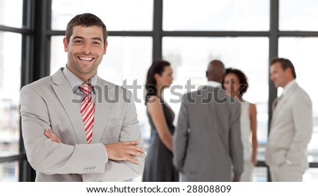 Potrait of a Smiling Businessman standing in Front of Business team