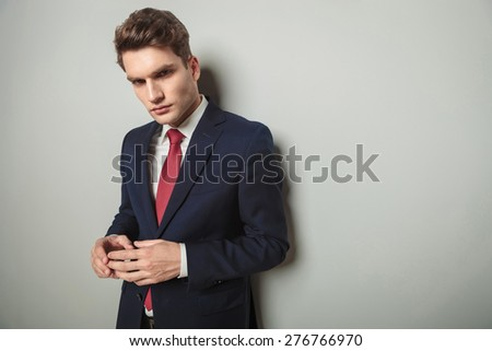 Potrait of a young business man thinking while holding his hands together. - stock photo