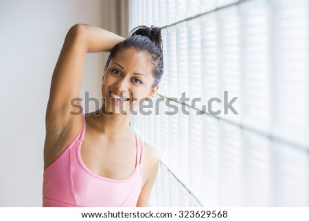 Potrait of a young latin woman indoors wearing leggins and a top, ready for her workout. - stock photo