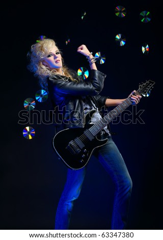 potrait of beautiful blonde girl glam rocker playing on electric guitar. shiny cds on dark background.