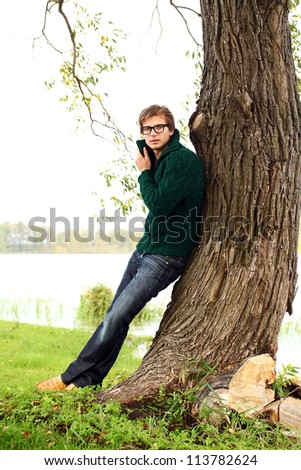 Potrait of handsome guy at cold autumn day in the park - stock photo