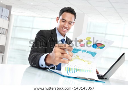 potrait of successful businessman showing growth chart and smiling