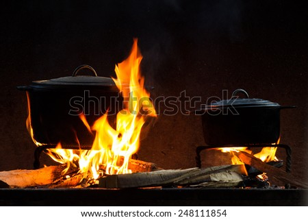 Pots and pans on the stove over a natural fire for cooking  - stock photo