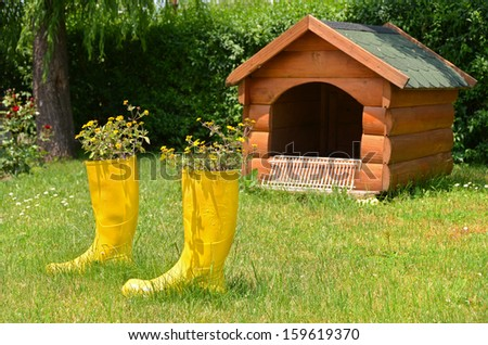 pots of flowers in a boot and dog house - stock photo