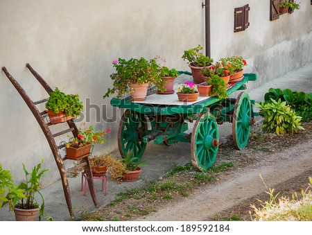 Pots with flowers on top of green wooden cart as part of rural garden decoration in Piedmont, Italy. - stock photo