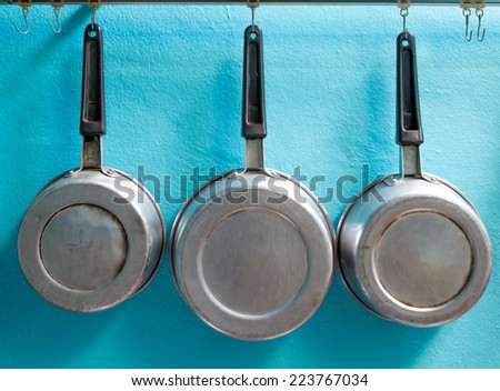 Pots with hanging on the blue wall - stock photo