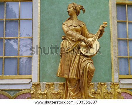 POTSDAM, GERMANY - SEPTEMBER 02, 2011: Golden statue in front of the Chinese house, part of Sanssouci park(18th century) is the former summer palace of Frederick the Great, King of Prussia.