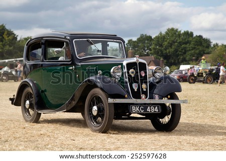 POTTEN END, UK - JULY 27: A vintage Austin 8 motorcar leaves the main show arena after being displayed to the public at the Dacorum Steam & Country fair on July 27, 2014 in Potten End - stock photo