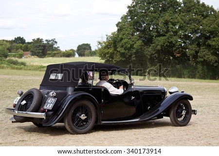 POTTEN END, UK - JULY 27: A vintage 1934 Jaguar SS1 luxury tourer car exits the show grounds having given a public display earlier in the day at the Dacorum Steam Fair on July 27, 2014 in Potten End.