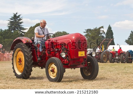 POTTEN END, UK - JULY 27:  As part of the agricultural theme of the show, a vintage tractor gives a display in the main arena to the public at the Dacorum Steam fair on July 27, 2014 in Potten End  - stock photo