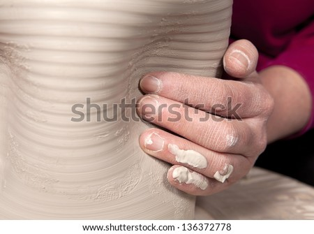 Potter's hand creating an impression in vase - stock photo