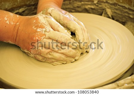 Potter's hands on the lump of clay on the wheel - stock photo