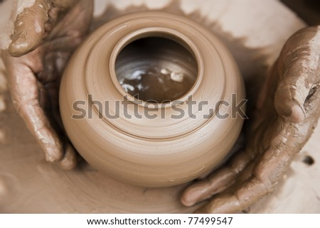 potter's hands shaping up the terracotta pot - stock photo