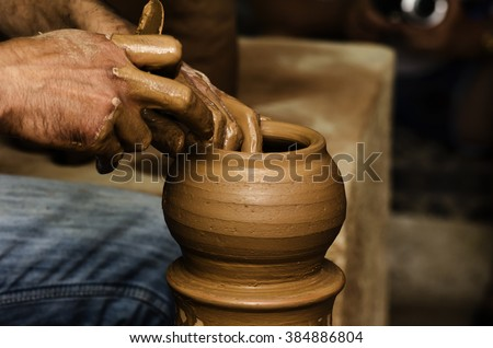 Potter shaping clay on the pottery wheel - stock photo