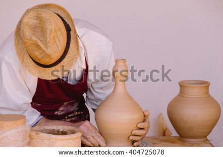 Potter with apron and hat modelling a clay vase by hand using a kick wheel - stock photo