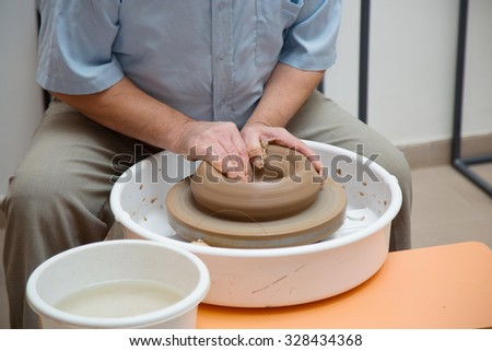 potter working on ceramic jug by hands