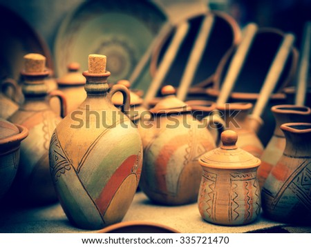 Pottery jar and coffee kettles on the rural fairs in Ukraine. Handmade clay potters in old traditions. Craft pottery utensil on a folk festival. - stock photo